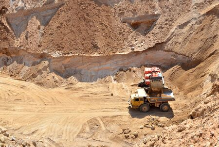 Excavator developing the sand on the opencast and loading it to the heavy dump truck. Processing of loose material in mining quarry. Drill, breaking, processing plant, crushing and screening - Image Stock Photo