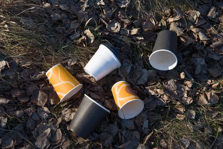 People throw paper coffee cups on ground. The problem of environmental pollution. Pile of abandoned coffee cups on grass in the park