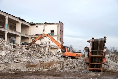 High Reach Excavator machines for demolition of tall building. Machine with hydraulic shears for demolish. Hydraulic Crushing Hammer destroys concrete of the old structures. Scrap metal shears