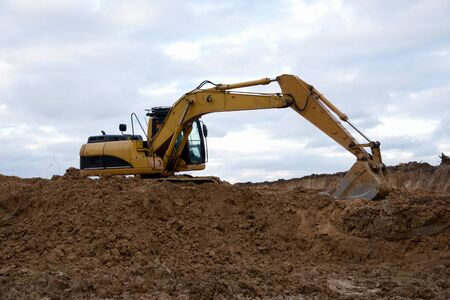 Excavator at earthworks on construction site. Backhoe loader digs a pit for the construction of the foundation. Digging trench for laying sewer pipes drainage in ground. Earth-Moving Heavy Equipment Foto de archivo