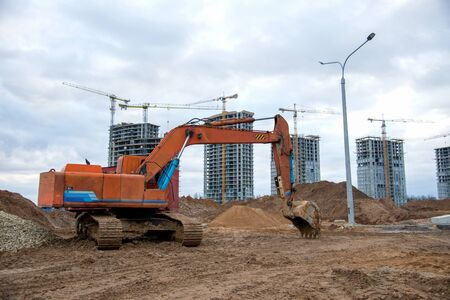 Excavator working at construction site. Backhoe digs ground for the foundation and for paving out sewer line. Construction machinery for excavating, loading, lifting and hauling of cargo on job sites