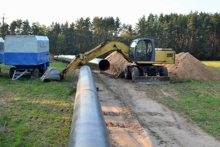Excavator digs ground for the installation of industrial gas and oil pipes. Natural gas pipeline construction work. A dug trench in the ground. Backhoe the digging pipeline ditch.