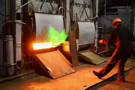 Steel quenching at high temperature in industrial furnace at the workshop of a forge plant. Process of cooling, heat treatmen. Blacksmith and metallurgical industry, steelmaking, hot rolling mill Stock Photo
