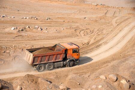 Orange dump truck transports sand in an open pit mine. In the production of reinforced concrete products, concrete for the construction of buildings using coarse sand. Mining industry Foto de archivo