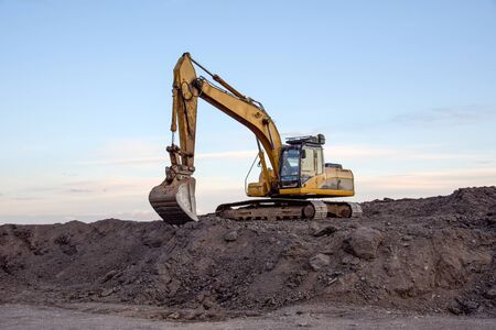 Excavator working at open pit mining on sunset background. Backhoe digs gravel in sand quarry on blue sky background. Recycling old asphalt at a landfill for the disposal of construction waste Stock Photo