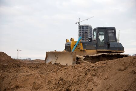 Bulldozer with bucket for pool excavation and utility trenching. Dozers during land clearing and foundation digging. Earth-moving equipment at construction site