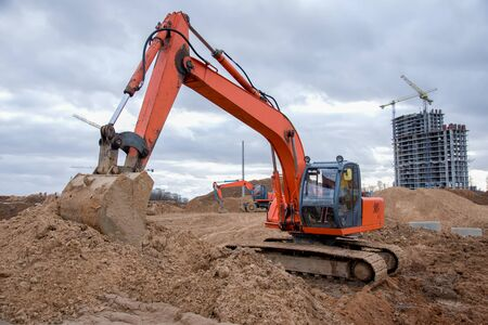Red excavator during earthworks at construction site. Backhoe digging the ground for the foundation and for laying sewer pipes district heating. Earth-moving heavy equipment