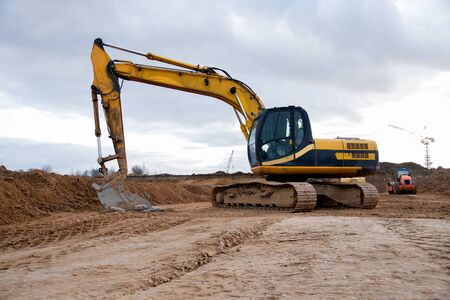 Yellow excavator during earthworks at construction site. Backhoe digging the ground for the foundation and for laying sewer pipes district heating. Earth-moving heavy equipment Foto de archivo