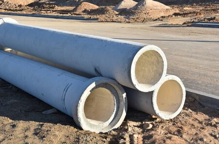Concrete drainage pipes at the construction site. Laying of underground storm sewer pipes. Installation of water main, sanitary sewer. Installation of concrete sewer wells in the ground
