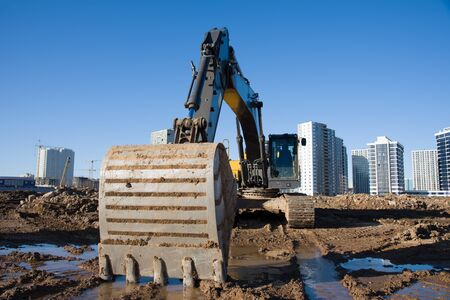 Excavator during earthmoving at construction site on blue sky background. Backhoe digging the ground for the foundation and for laying sewer pipes district heating. Earth-moving heavy equipment Фото со стока