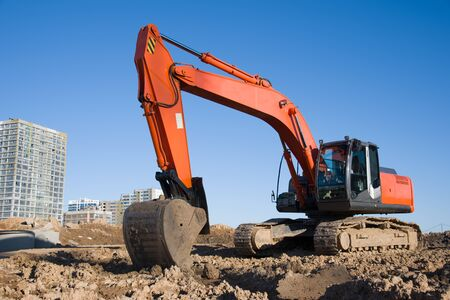 Excavator during earthmoving at construction site. Backhoe digg ground at construction site for the construction of the road and laying sewer pipes district heating. Earth-moving heavy equipment Фото со стока