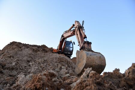 Excavator during earthmoving work at open-pit mining on sunset background. Loader machine with bucket in sand quarry. Backhoe digging th ground for the foundation and for laying sewer pipes