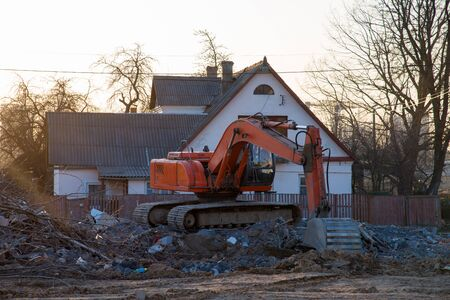 Excavator demolishes an old wooden house in the village for new construction project. Tearing Down a Houses. Building removal made of bricks. Hard equipment for demolition works