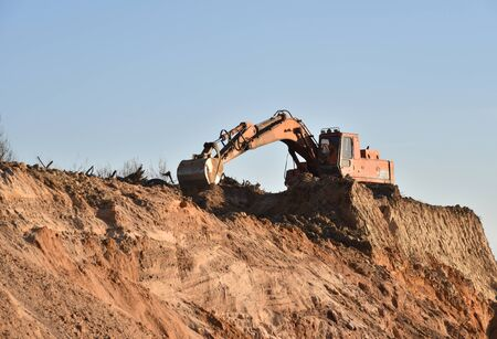 Large excavator working at construction site. Backhoe during earthworks on sand quarry. Earth-moving heavy equipment