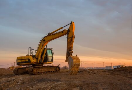 Excavator on earthworks at construction site on sunset background. Backhoe digs ground for the foundation and for paving out sewer line. Construction machinery for excavating