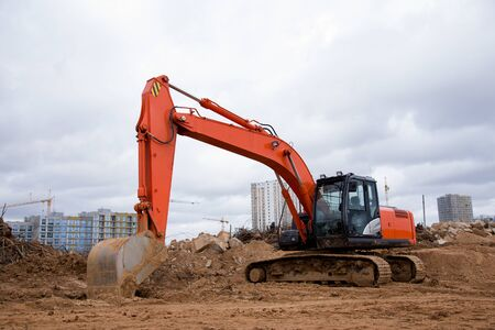 Red excavator during earthmoving at construction site. Backhoe dig ground for the construction of foundation and laying sewer pipes district heating. Earth-moving heavy equipment on road works