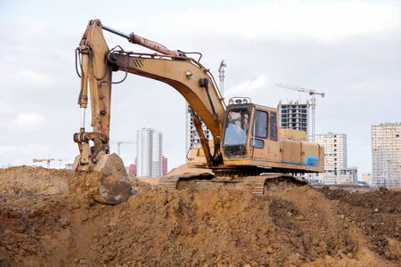 Yellow excavator during earthworks at construction site. Backhoe digging the ground for the foundation and for laying sewer pipes district heating. Earth-moving heavy equipment 스톡 콘텐츠