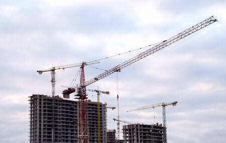 Tower cranes at large scale construction site against blue sky. Construction crane. Formwork solutions for reinforced construction and framed superstructure. Ð¡oncept of renovation of new housing
