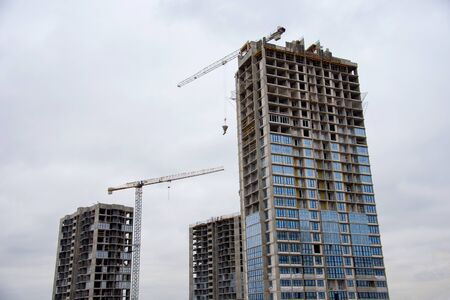 Tower cranes working at construction site against blue sky. Crane lifting a concrete bucket. Construction process of the new residential buildings. Transportation blocks and pouring of the cement mix