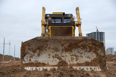 Bulldozer during land clearing and foundation digging at large construction site.  Crawler tractor with bucket for pool excavation and utility trenching. Dozer, Earth-moving equipment 스톡 콘텐츠