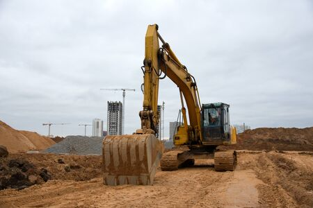 Excavators at earthworks on construction site. Backhoe loader digs a pit for the construction of the road. Digging trench for laying sewer pipes drainage in ground. Earth-Moving Heavy Equipment
