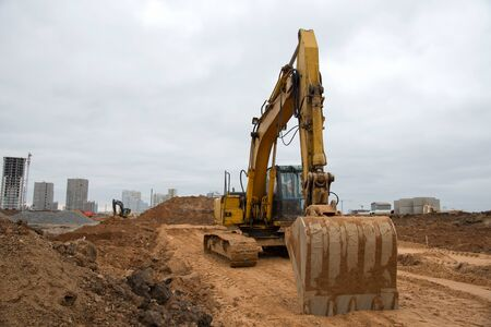 Track-type excavator during earthmoving at construction site. Backhoe digging the ground for the foundation and for laying sewer pipes district heating. Earth-moving heavy equipment 스톡 콘텐츠
