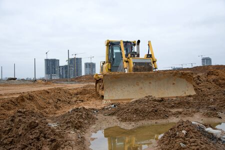 Dozer with bucket for pool excavation and utility trenching. Bulldozer during land clearing and foundation digging at construction site. Earth-moving equipment background