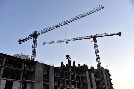 Silhouettes of tower cranes constructing a new residential building at a construction site on sunset background. Crane lifting a concrete bucket. Builders pouring cement mix for formworks. Soft focus