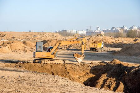 Large excavator working at construction site. Backhoe during earthworks on sand open-pit. Digging ground for the foundation and for laying sewer pipes district heating. Earth-moving heavy equipment 스톡 콘텐츠