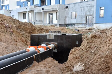 Laying heating pipes in a trench at construction site. Install underground storm systems of water main and sanitary sewer. Cold and hot water, heating and heating system of apartments in the house Фото со стока