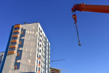 Crane hook on lifting fears and chains hanging of the mobile auto crane on a background construction resedental building and blue sky. Concept of renovation program