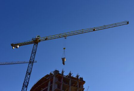 Tower cranes in action on blue sky background. Preparing to pour a bucket of concrete into formwork. rane lifting cement bucket during construction a multi-storey residential building
