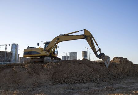Excavator working at construction site. Backhoe during earthworks. Digging ground for the foundation and for laying sewer pipes district heating. Earth-moving heavy equipment Banco de Imagens