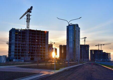 View on the large construction site with tower cranes and buildings on sunset background. Multi-storey residential building is being constructed use of crane. Concept of renovation program
