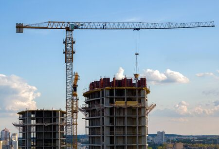 Tower crane in action on blue sky background. Preparing to pour a bucket of concrete into formwork. rane lifting cement bucket during construction a multi-storey residential building Banco de Imagens