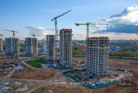 View on the large construction site at urban area. Tower cranes in action with machinery and builders. Multi-storey residential Building is being constructed use of crane. Pour of concrete in formwork
