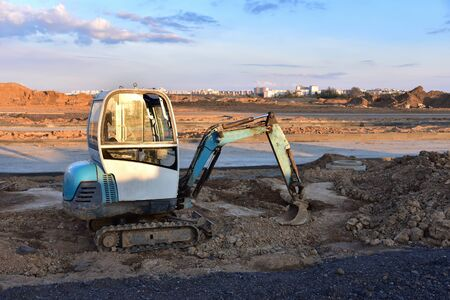 Mini excavator digg trench to lay cables concrete curbs and paving slabs at construction site. Backhoe on earthwork roadworks