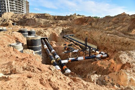 Laying heating pipes in trench at construction site. Installing concrete sewer wells and underground storm systems of sanitary water main. Cold and hot water heating system of the apartments in house Reklamní fotografie