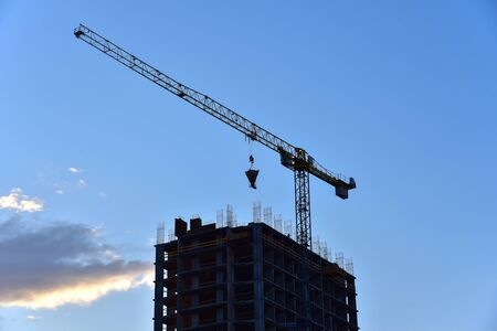 Silhouette of tower crane in action on sunset background. Preparing to pour a bucket of concrete into formwork. rane lifting cement bucket during construction a multi-storey residential building