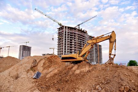 Excavator during earthmoving at construction site on sunset background. onstruction machinery for excavating. Tower cranes lifting a concrete bucket for pouring of concrete into formwork