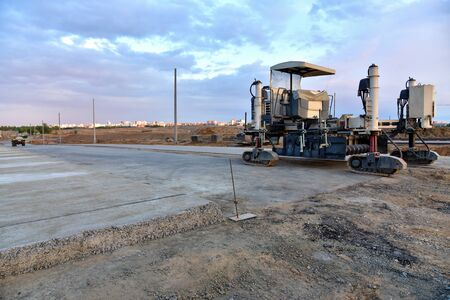 Slipform paver machine on road work at construction site. Highway concrete paving in the new quarter. Repairing concrete roads using new technology