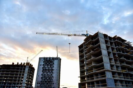 Tower crane in action on sunset sky background