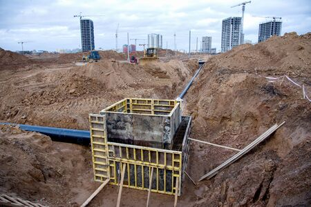 Concrete pile in formwork frame for construct stormwater and underground utilities, pump stations, sewers pipes. Connecting a heating sistem to a concrete sewer wells structure at construction site.