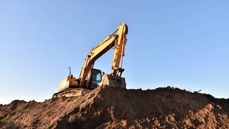 Excavator working at construction site. Backhoe digs ground in sand quarry on blue sky background. Construction machinery for excavation, loading, lifting and hauling of cargo on job sites