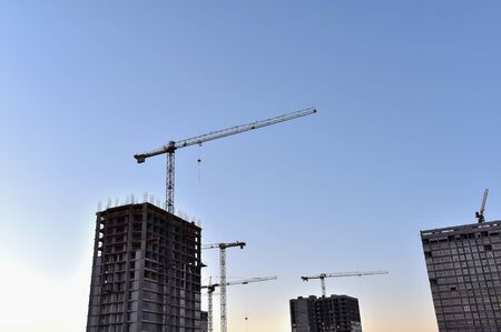 Tower cranes against the blue sky during sunset. Construction of a new high-rise apartment buildings from concrete blocks and gas-silicate brick. Renovation program, concept of the buildings industry.