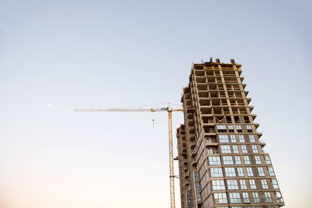 Tower crane against the blue sky during sunset. Construction of a new high-rise apartment building from concrete blocks and gas-silicate brick. Renovation program, concept of the buildings industry