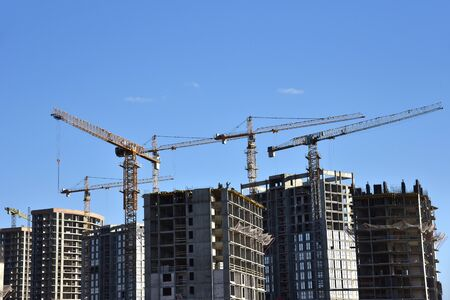 Tower crane constructing a new residential building at a construction site against blue sky. Renovation program, development, concept of the buildings industry. Stock fotó