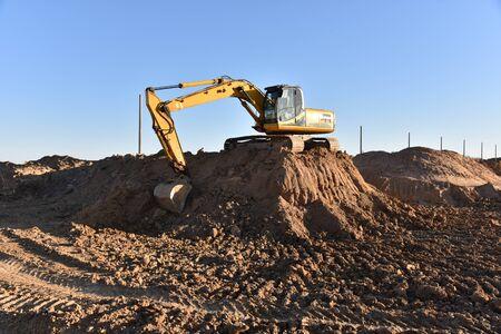 Ausheben des Grubenfundaments ein Loch mit Bagger. Für den Bau des Grabens sind Erdarbeiten beim Ausheben und Verfüllen des Bodens bis zur erforderlichen Tiefe erforderlich. Baumaschinen für Erdbewegung