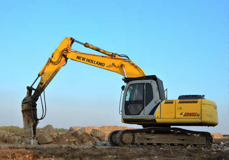 Minsk, Belarus 02.09.2019: Excavator New Holland E215B with hydraulic breaker hammer for the destruction of concrete and hard rock at the construction site or quarry. Jackhammer background Editorial