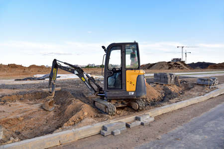 Minsk/Belarus, MAY 15, 2020: Mini Excavator VOLVO at constrruction site on road work. Laying paving slabs and borders. Process of installing paving bricks in the town